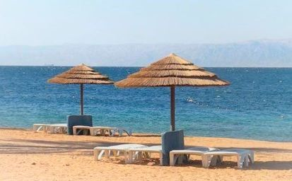 Due ombrelloni e delle sdraie sulla spiaggia di Aqaba